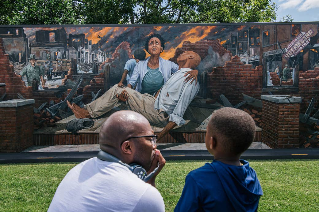 A man kneels down next to a young boy in front of a mural of a woman holding a man and Tulsa burning