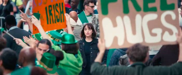 """Alice walking down the street through a Saint Patrick's Day parade in """"How To Be Single"""""""