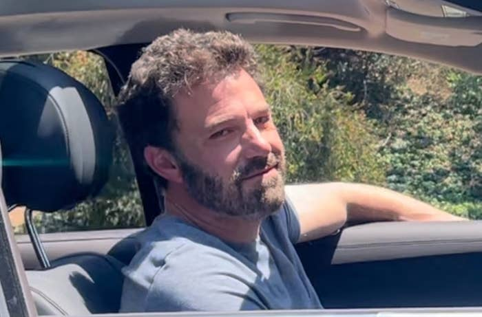 Ben smirks while sitting in the front seat of his car