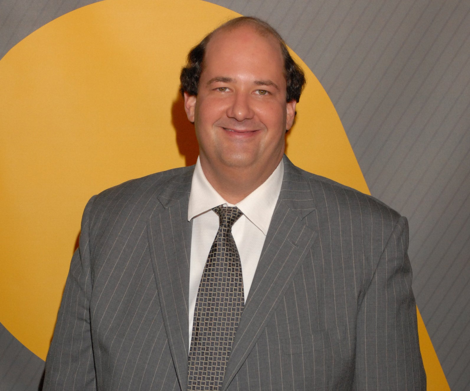 Brian appears at an event in a grey striped suit