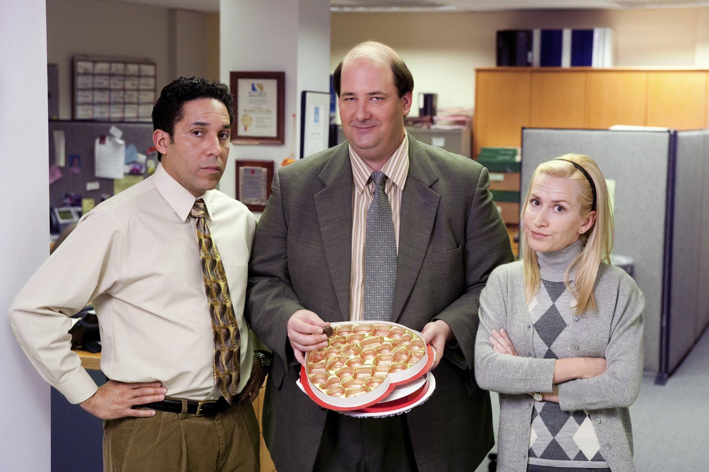 Kevin holds a box of chocolate next to his co-workers on The Office