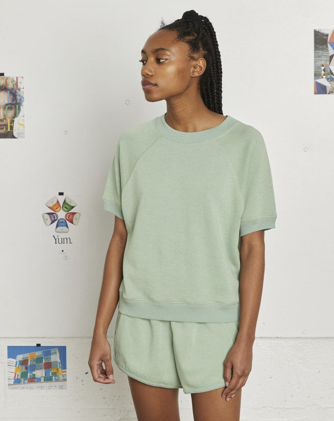model wearing the short-sleeved sweatshirt and sweat shorts in light green