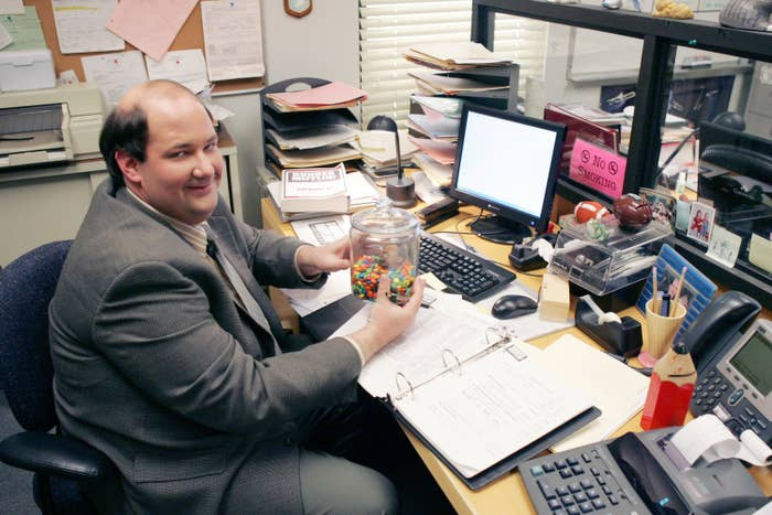 Kevin sits at his desk in a photo from The Office
