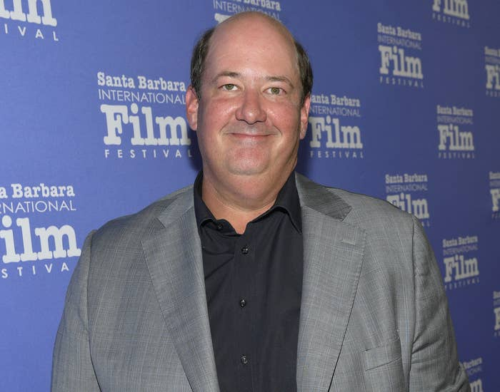 Brian wears a grey suit at a film festival