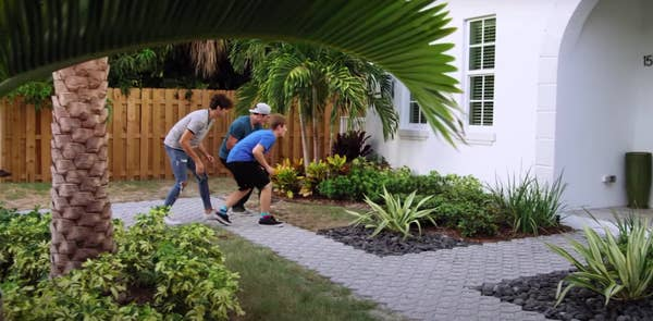 """Three boys trying to walk stealthily toward a house window in """"Swiped"""""""
