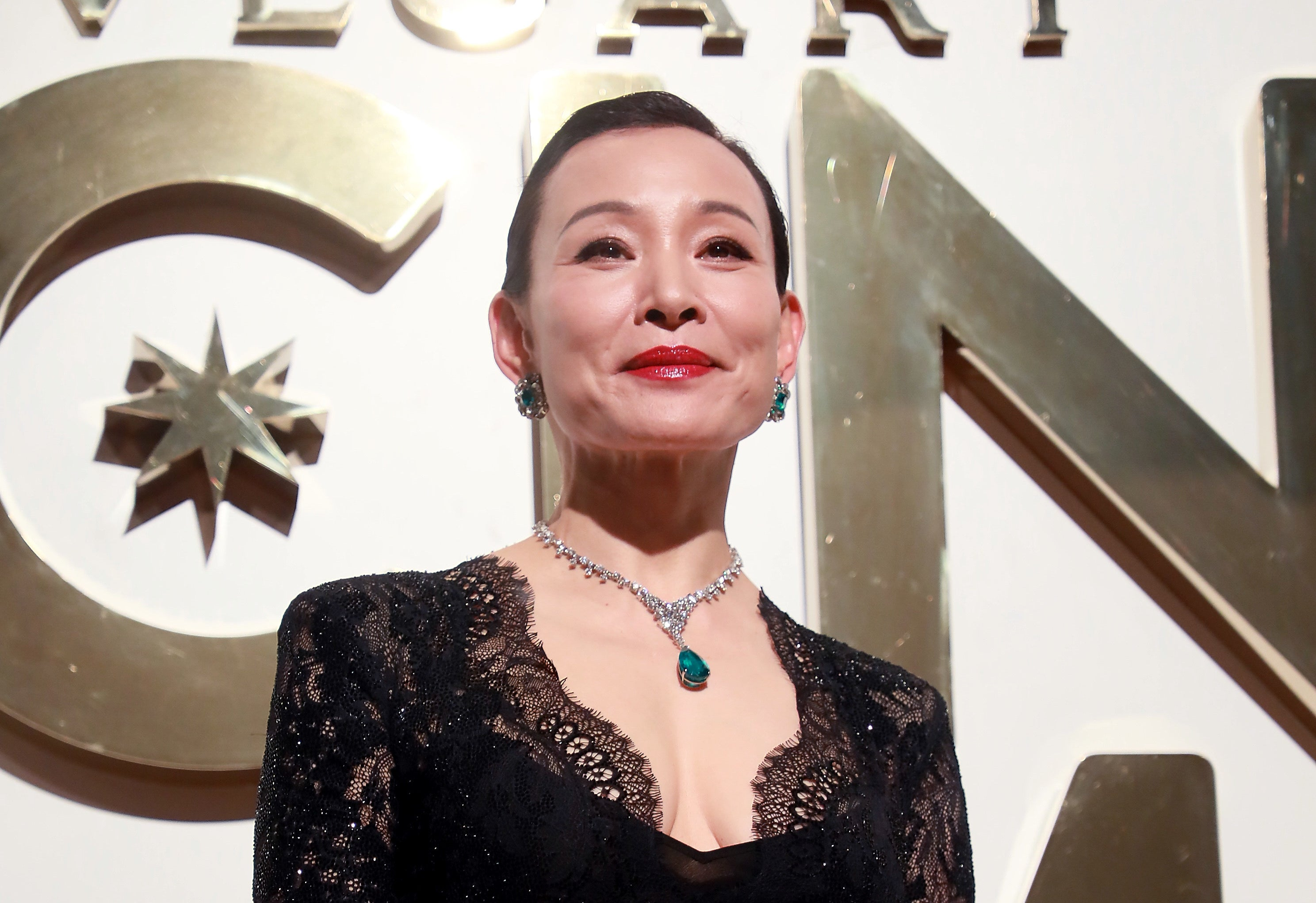 Joan Chen looking very regal in a lacy black outfit and bejeweled necklace