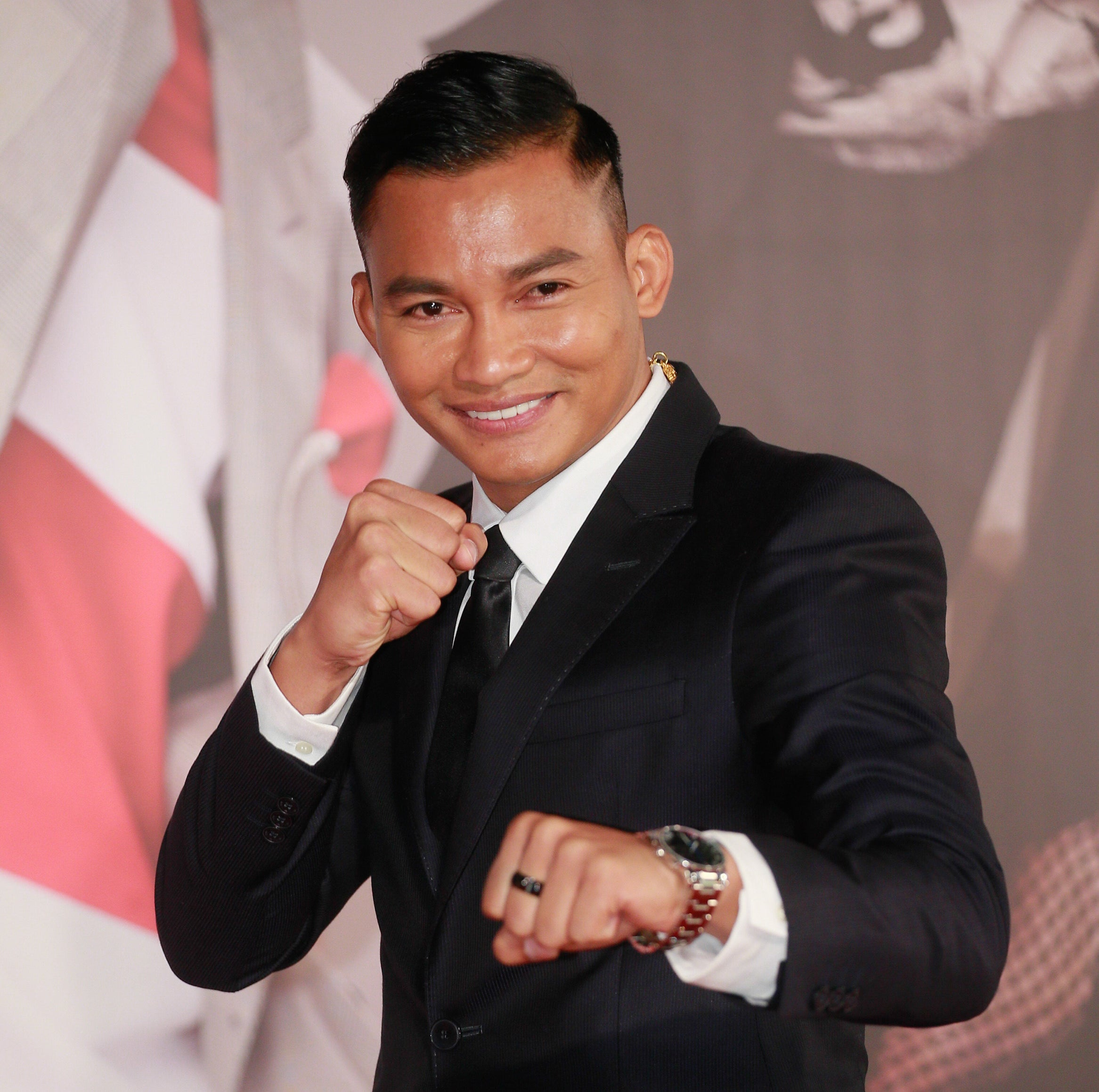 Tony Jaa smiles and holds up his fists