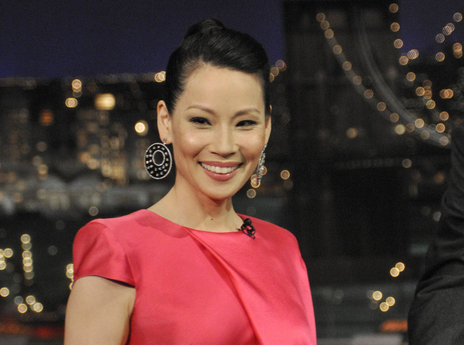 A smiling Lucy Liu wearing large earrings and a short-sleeved dress