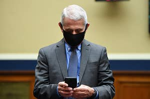 Dr. Fauci, wearing a black mask, looks at his cell phone