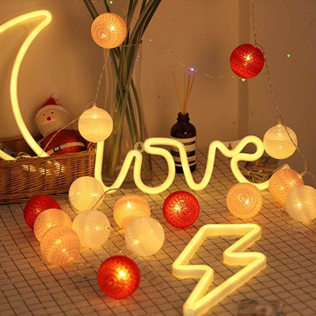 A neon light that says Love surrounded by different lights.