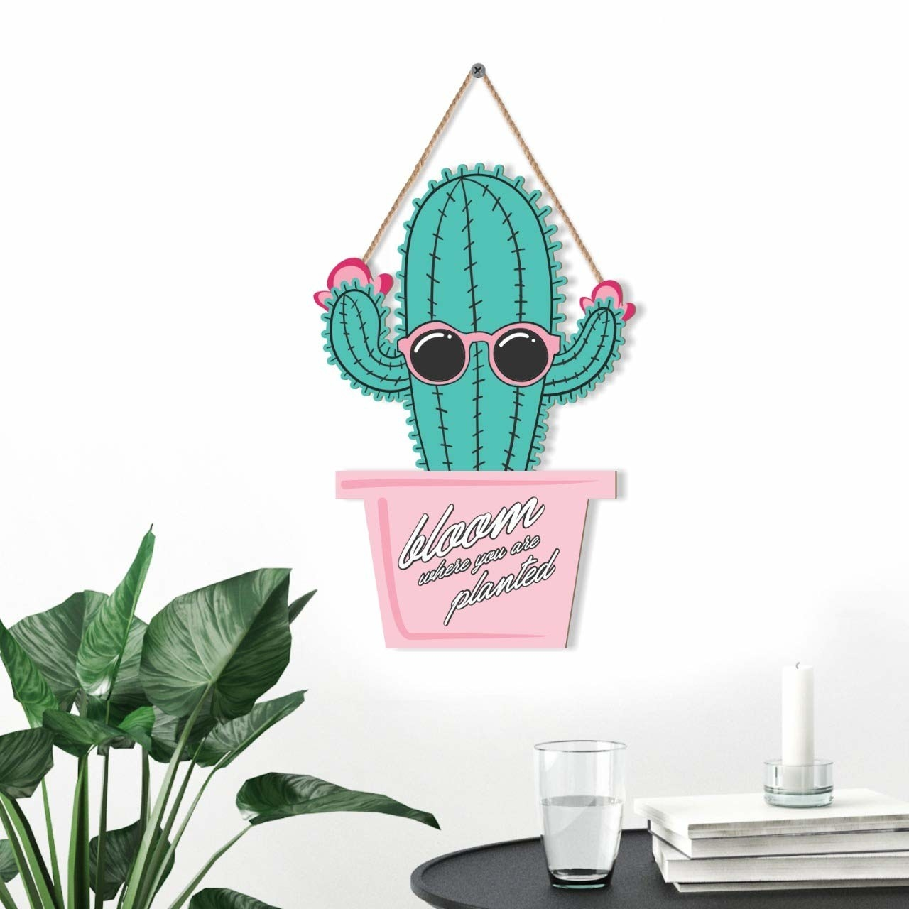 A wall hanging with a  cactus wearing sunglasses on a pink planter.