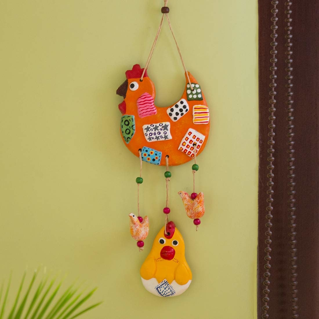 A chicken wall hanging with some chicks and a rooster at the bottom