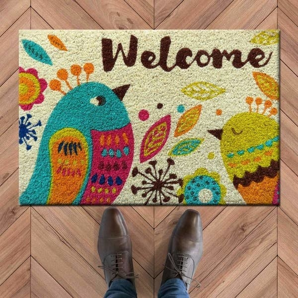 A doormat with colourful birds and the word 'Welcome' written on it and a person standing near it
