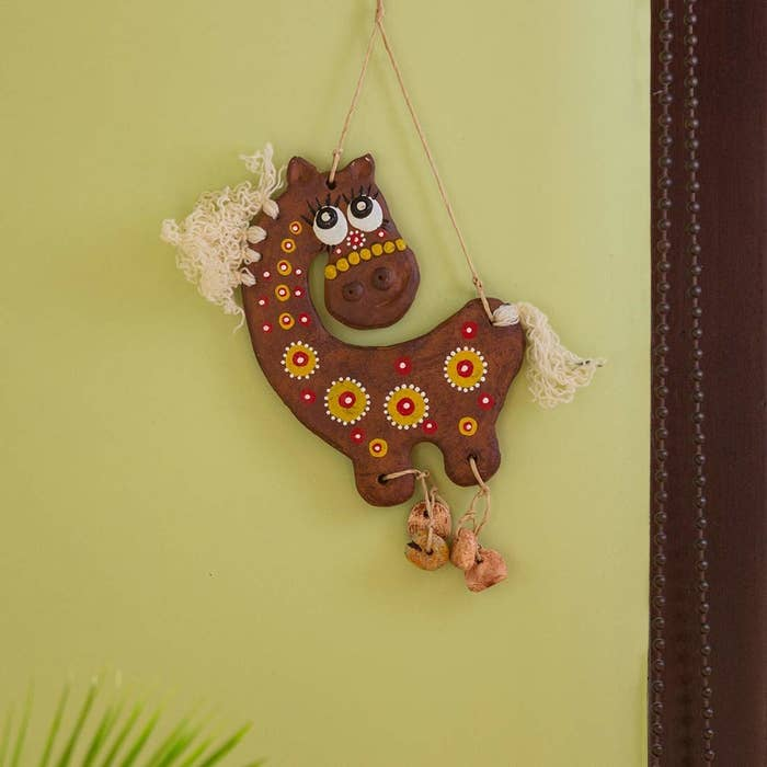 A terracotta horse with bells at the bottom on a wall