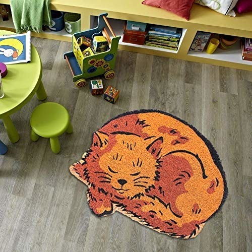 A ginger cat mat on the floor beside a mini table and stools