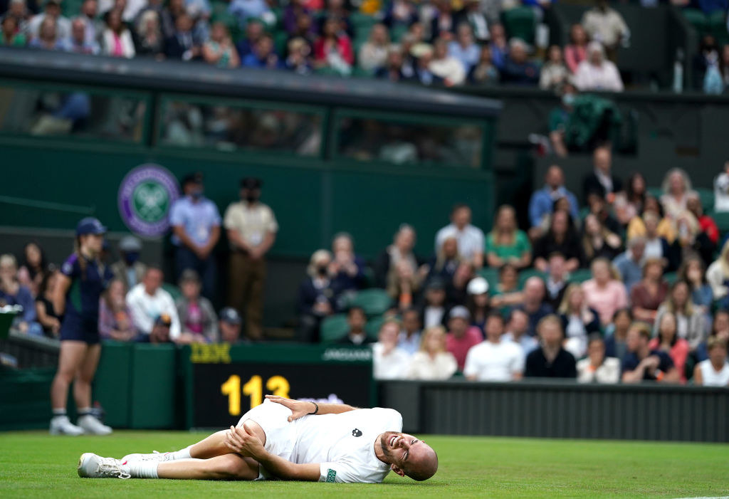 Adrian Mannarino is on the ground in visible pain during his match against Roger Federer