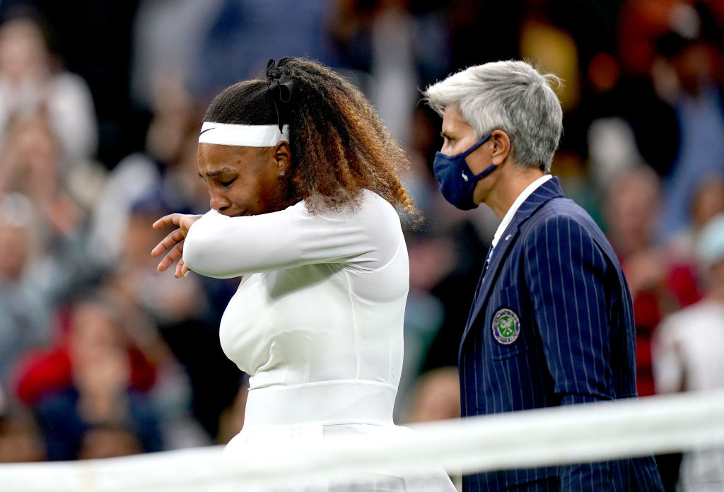 Serena Williams tries to hold back tears as she stands next to the umpire after injuring her right leg during her match