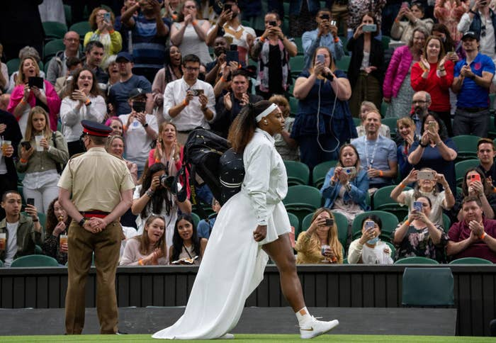 Serena Williams walks on court in a white dress and train before her first-round match at Wimbledon