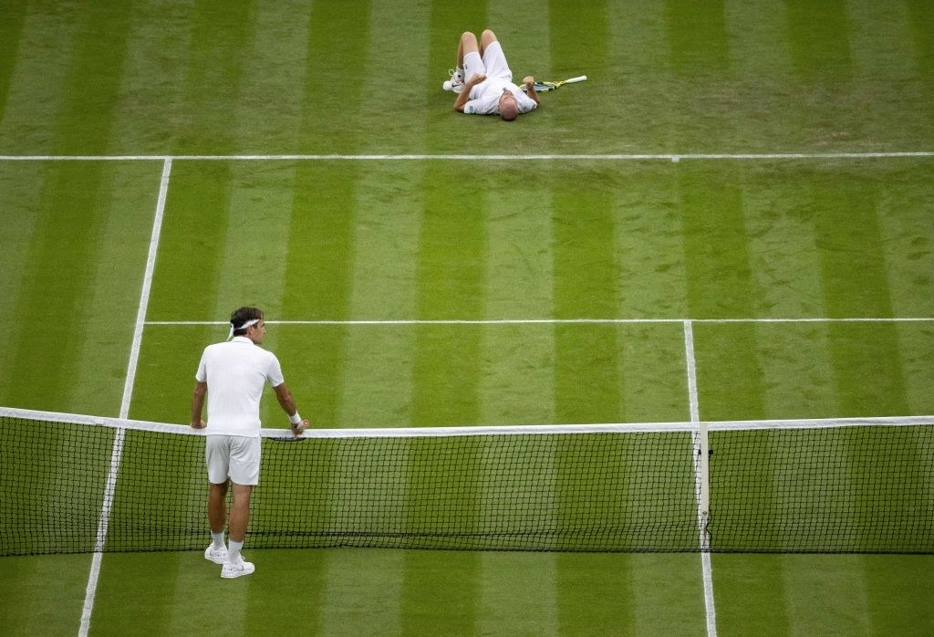 Roger Federer looks on with concern at the net as Adrian Mannarino lies on the ground after slipping on the grass