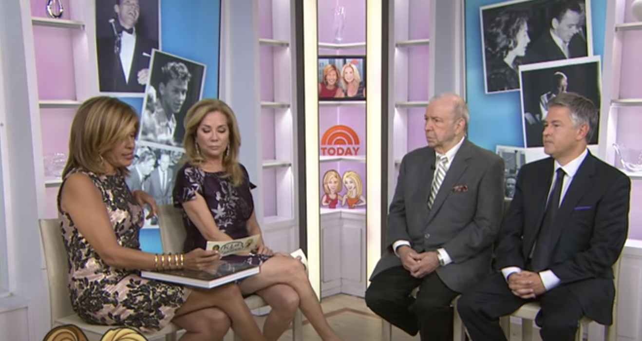 hoda and kathie lee looking at a note card while the guests sit nearby