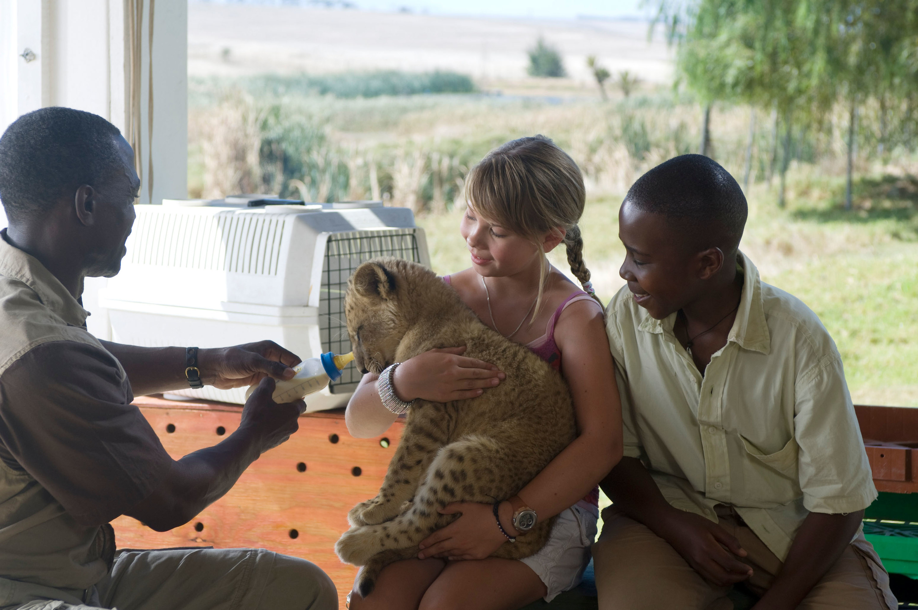 """Getmore Sithole, Bindi Irwin, and Siyabulela Ramba pose with a baby tiger on set of """"Free Willy: Escape from Pirate's Cove"""""""
