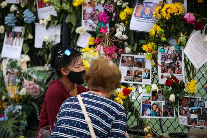 Two people stand in front of a fence covered in flowers and photos