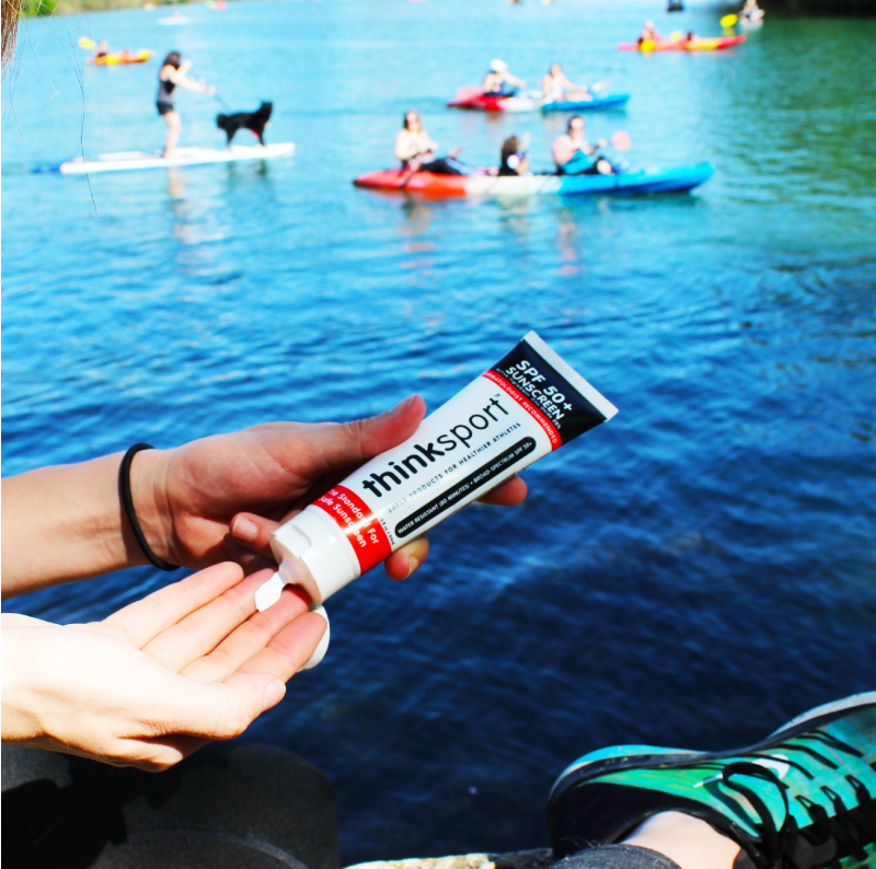person squeezing sunblock out of a thinksport bottle before going kayaking