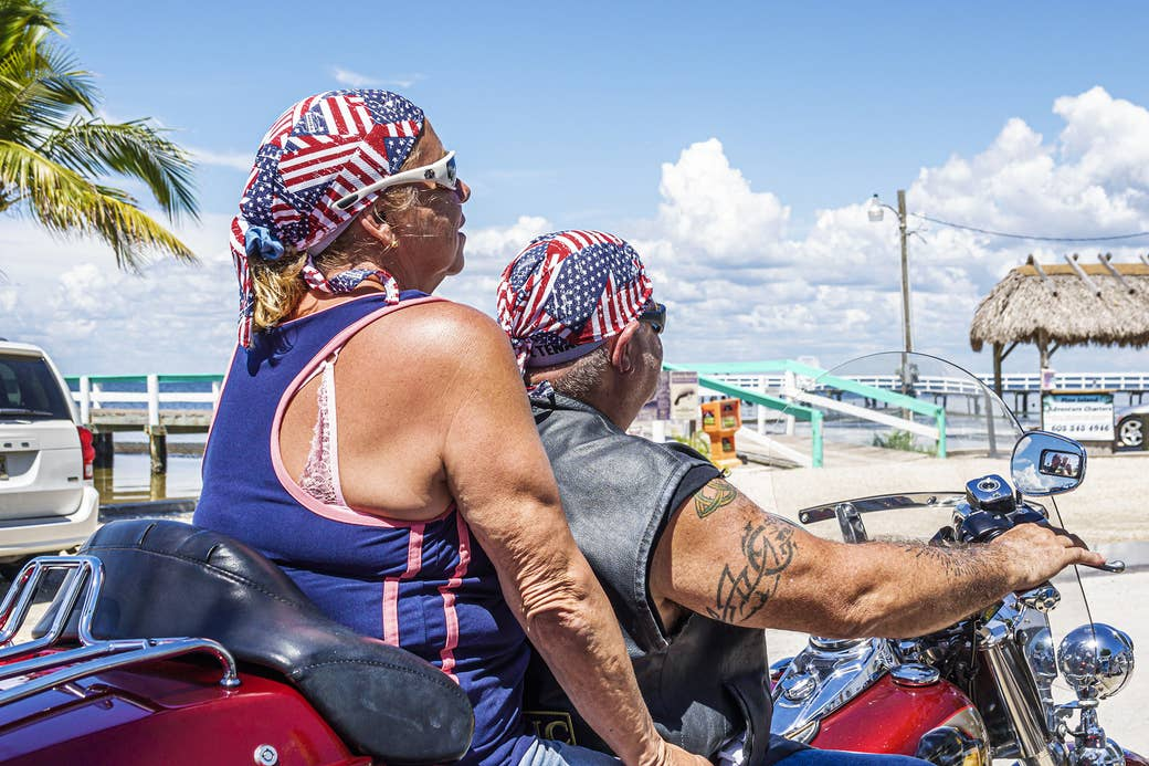Two people on a motorbike wear the US flag on their heads