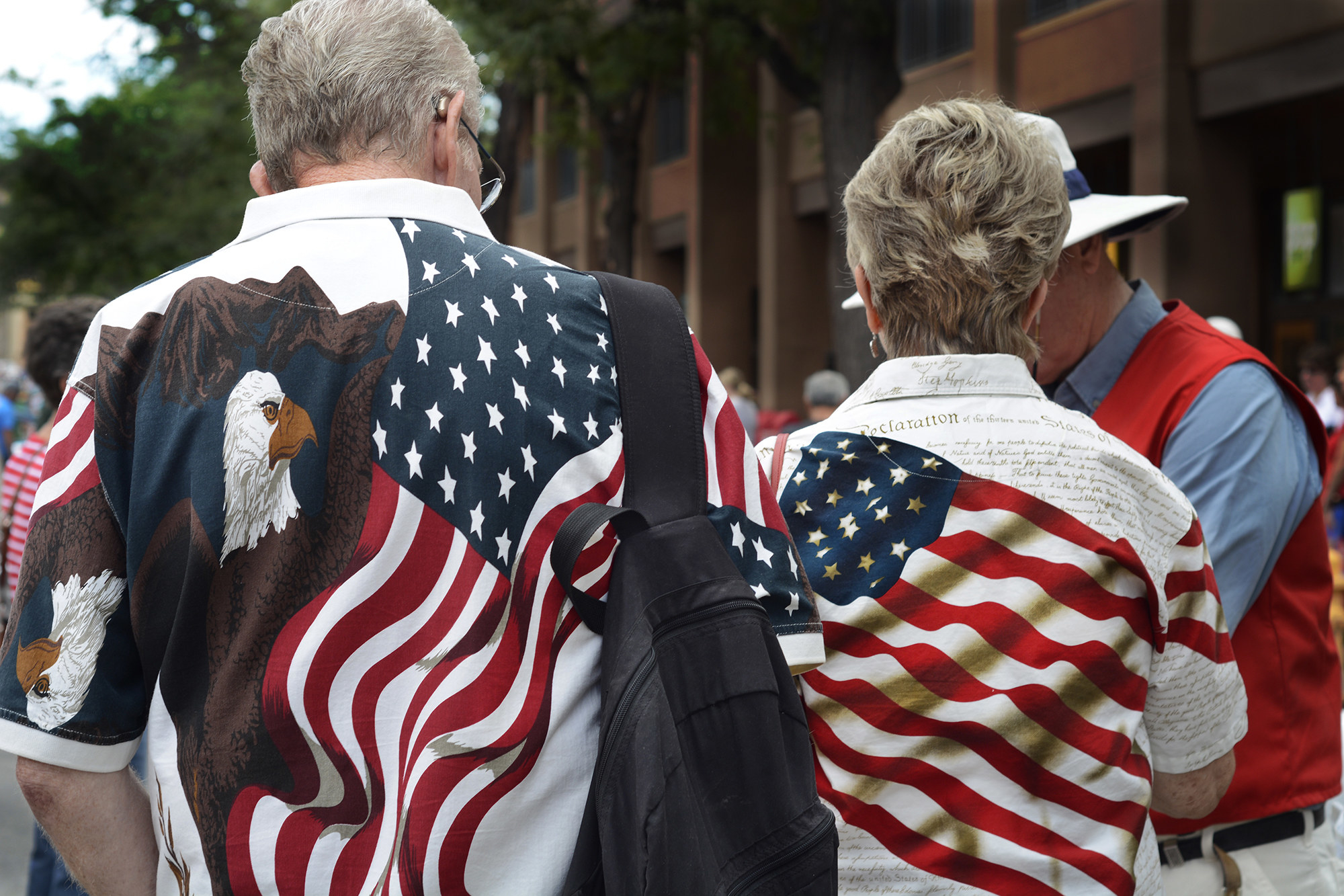 A man and a woman with their backs turned toward the camera wear flag-themed outfits, showing a bald eagle