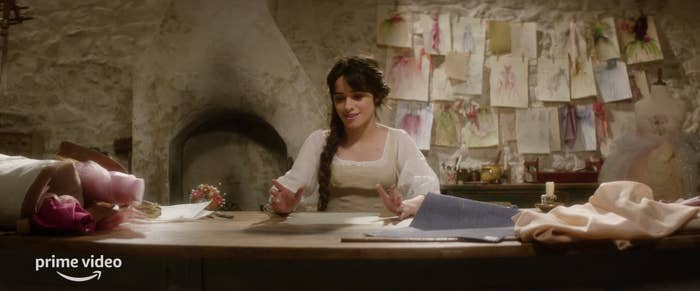 """Camila Cabello sits in front of her dress designs in the teaser trailer for Amazon Prime Video's """"Cinderella"""""""