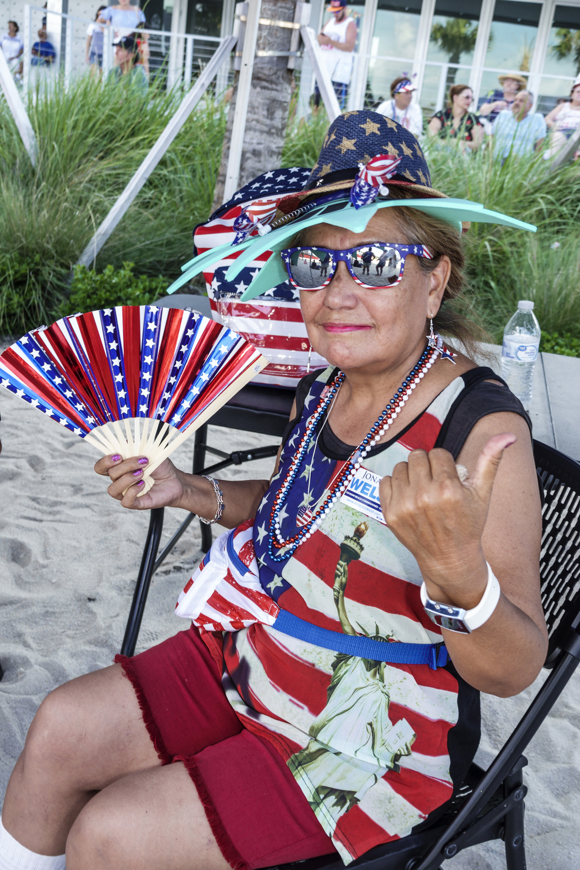 A woman wearing a flag hat with a flag fan and a flag shirt