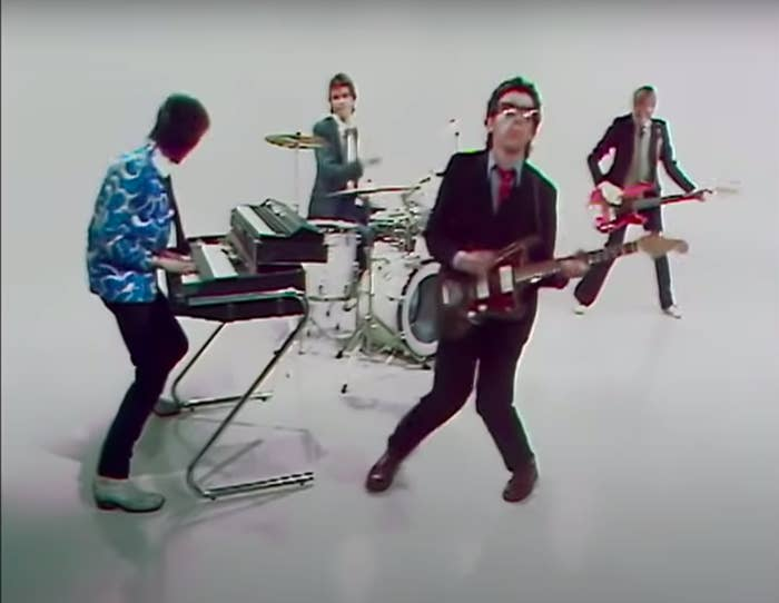 """A still from the music video for """"Pump it Up"""" showing Elvis and his band performing"""