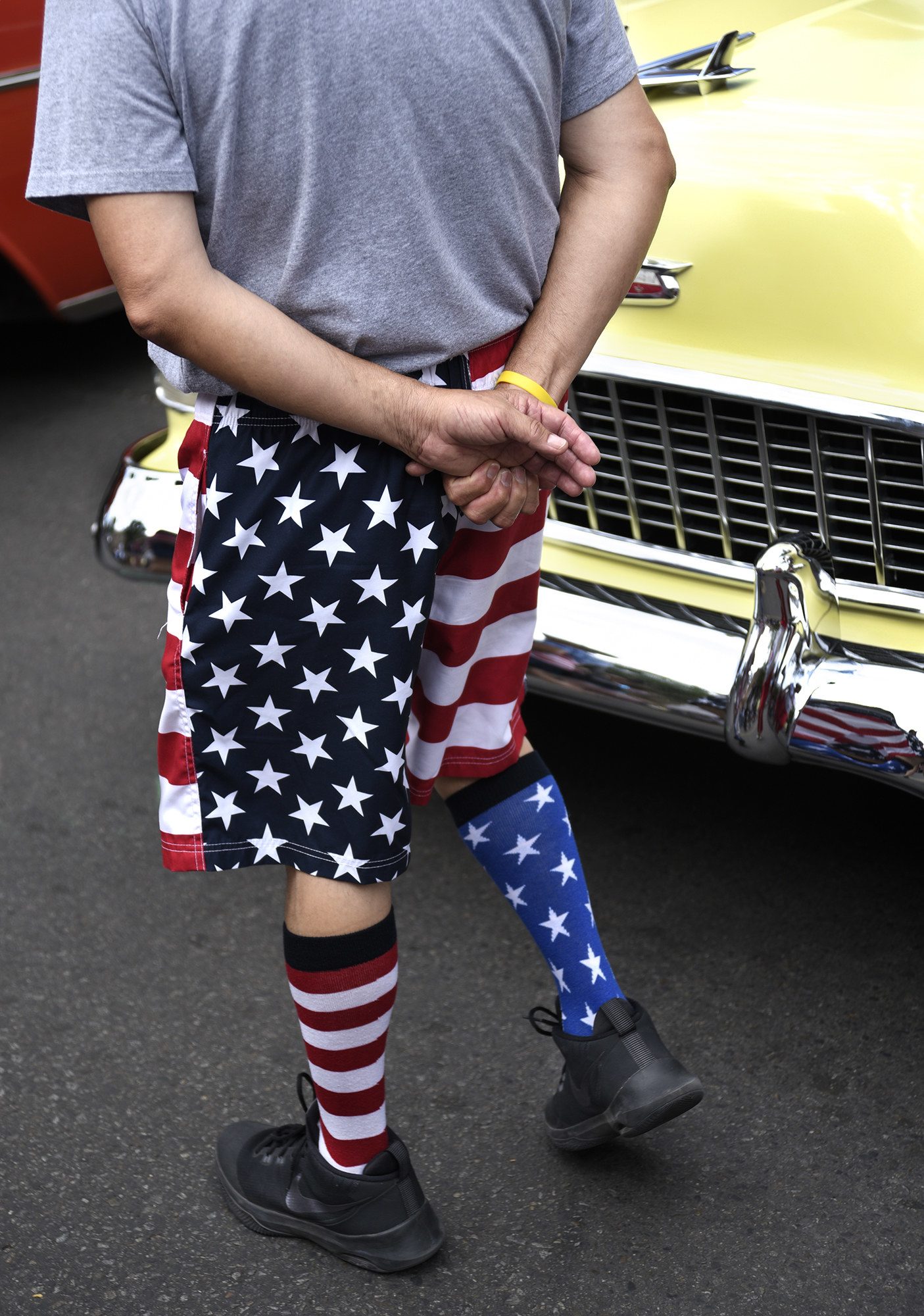A man walks with his hands behind his backs with US flag shorts and socks of different colors and patterns, showing different parts of the flag