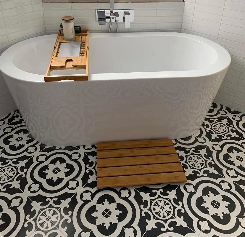 reviewer photo of the bamboo bath mat in front of a bath tub with a bamboo tray on it
