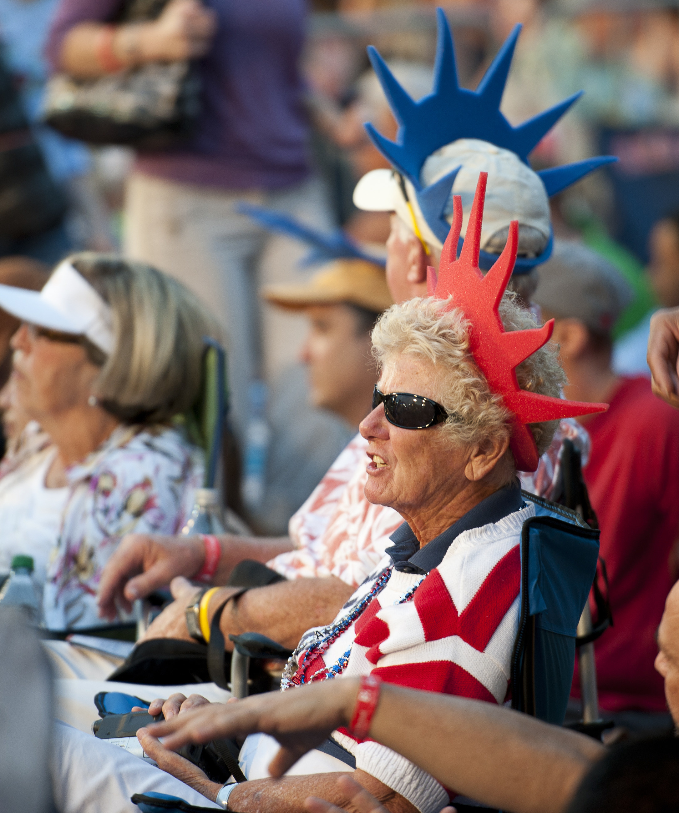 Close-up of a person wearing sunglasses and a US flag top and red Statue of Liberty–type crown
