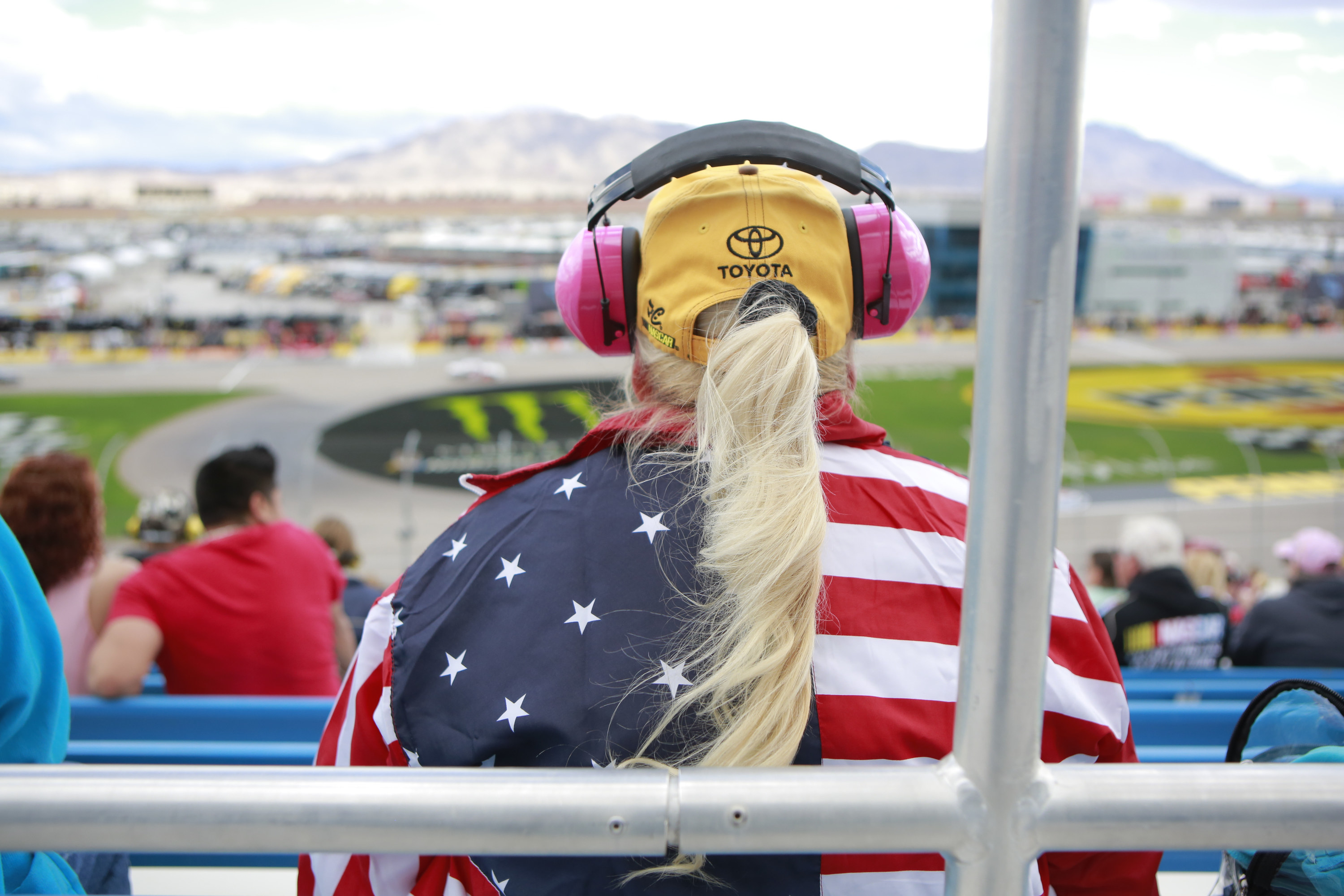 A person wearing an American flag shirt, Toyota cap, and large headphones sits with their back toward the camera