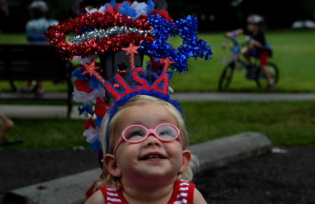 A toddler with a USA headband and red and white shirt