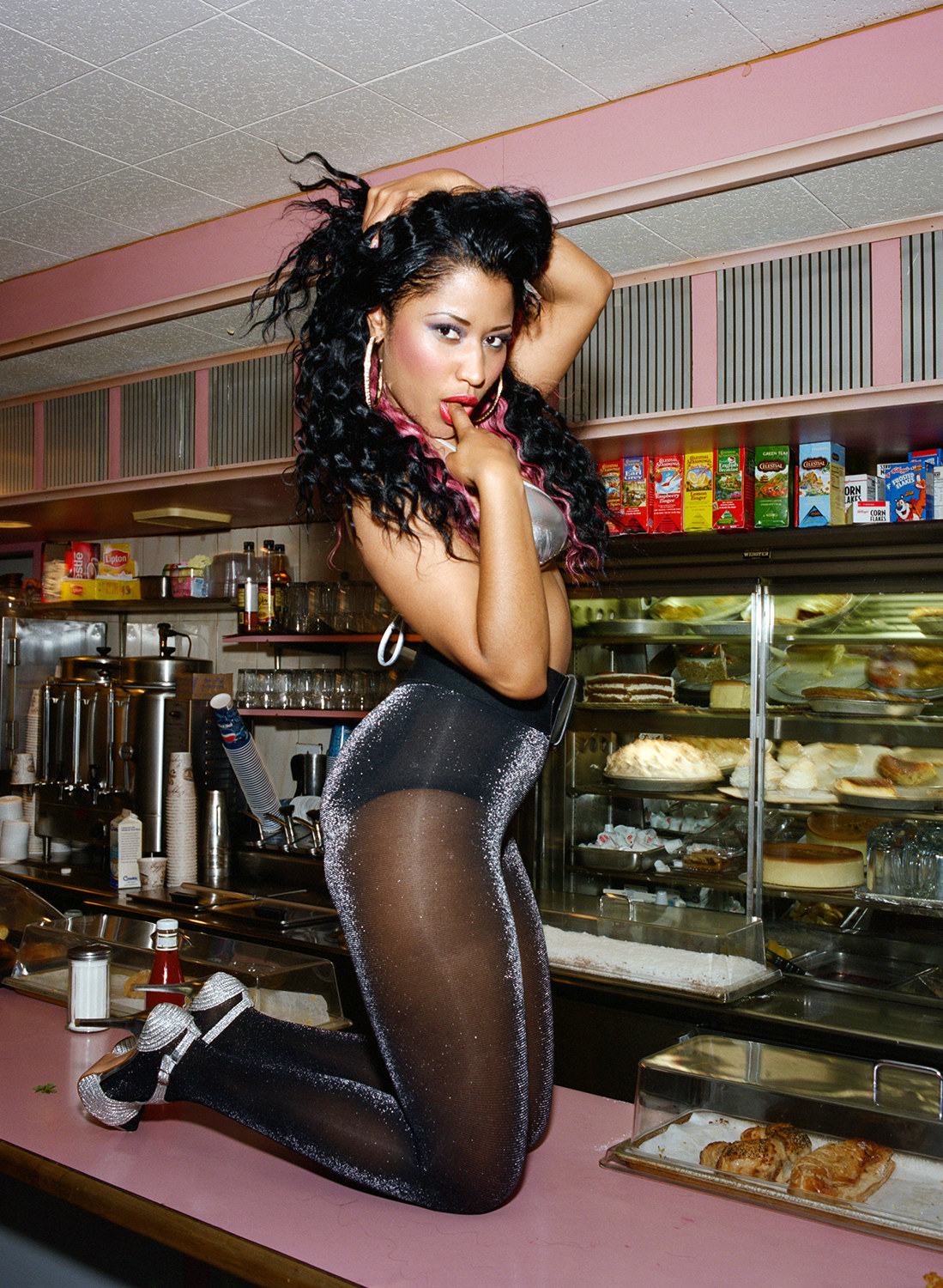 Nicki Minaj poses in sparkly tights on top of a diner counter