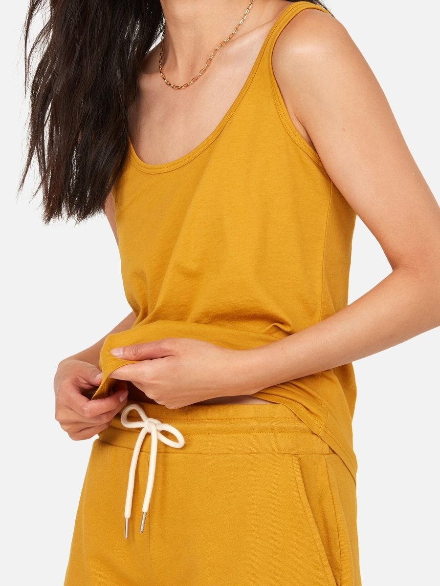 a model in a mustard yellow tank top