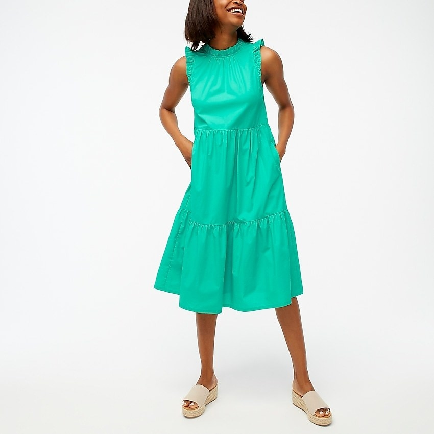 a model in a bright green tank dress with ruffled sleeves and a tiered skirt
