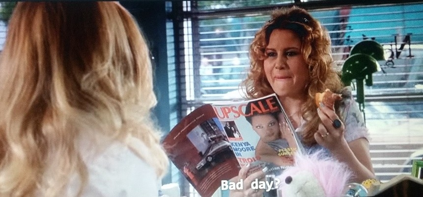 Paulette holds a magazine in her right hand and a half eaten donut in her left hand when she asks if Elle has been having a bad day.