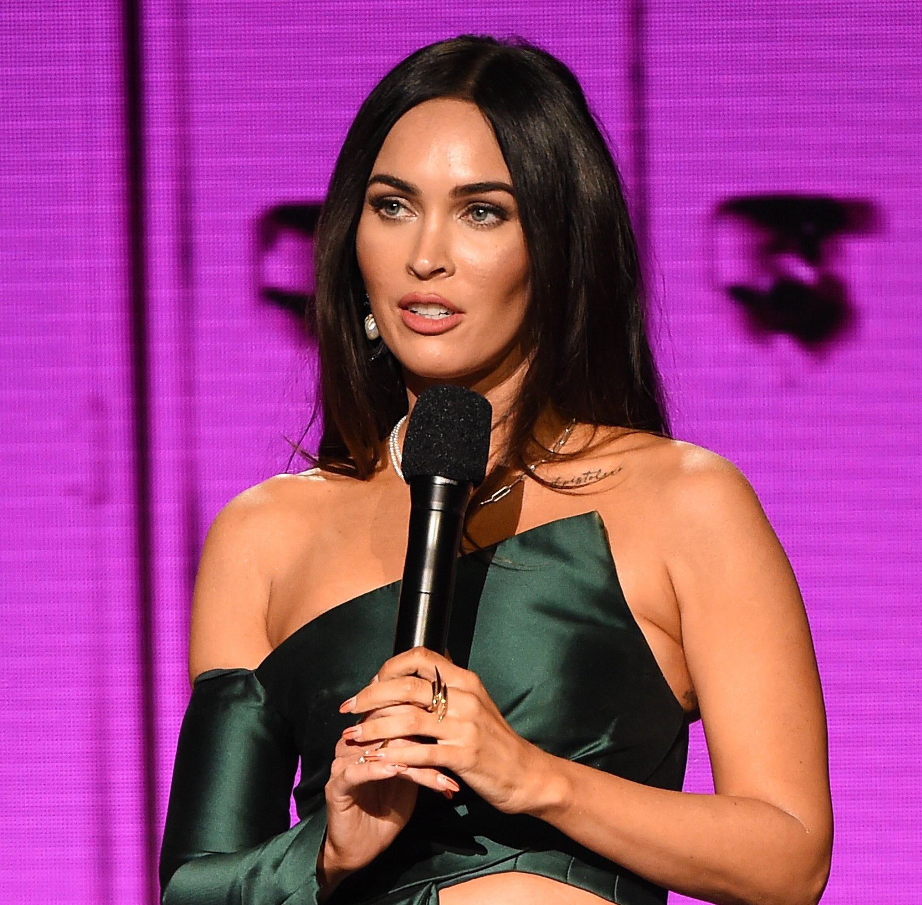 Megan Fox speaks into a microphone onstage at the 2020 American Music Awards