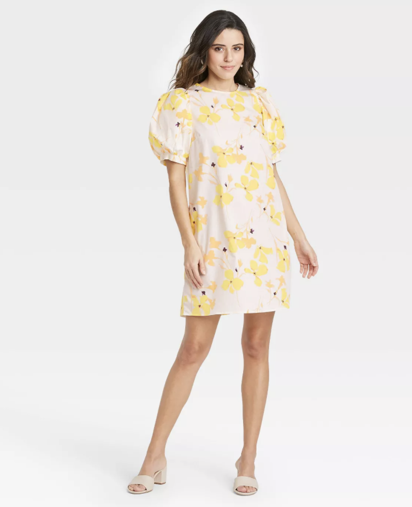 a model in a short tee dress with puffy cap sleeves and a yellow floral pattern