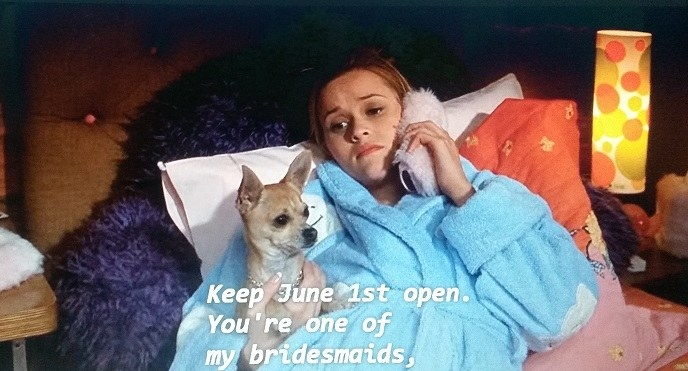 Elle is lying down on her bed wearing a blue bathrobe. She is holding a pink furry phone in her left hand and her dog Bruiser in her right hand