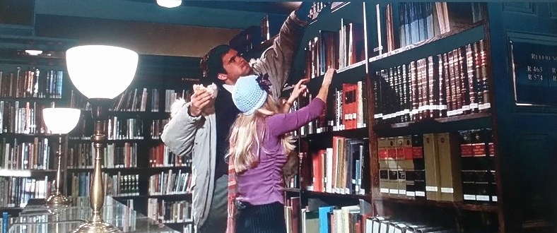 David Kidney easily reaches the top shelf of a library bookshelf to help Elle, who is wearing a purple sweatshirt and blue knit hat