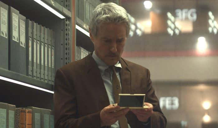 Mobius looking confused as he looks at a digital file