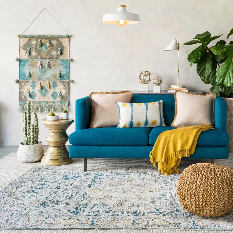 the khaki jute pouf ottoman in a living room with a teal couch