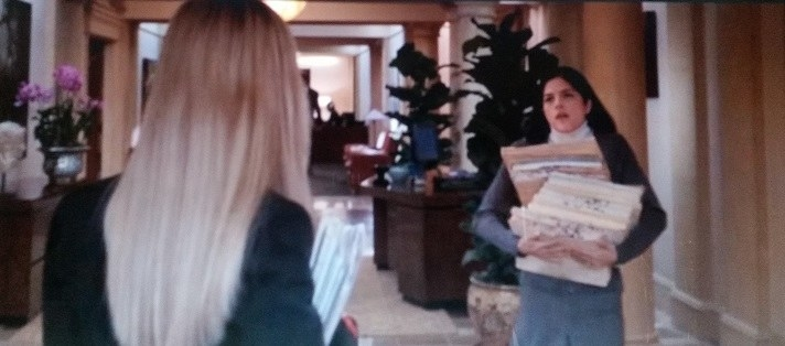 Vivian carries a large stack of files as she talks to Elle whose back is to the camera