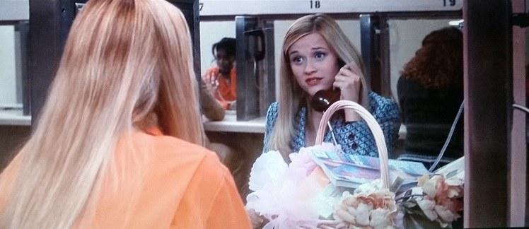 Elle talks to Brooke in prison. Next to Elle is a gift basket