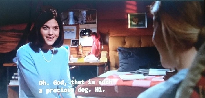 Vivian, wearing a blue sweatshirt and pearls, compliments Elle's dog